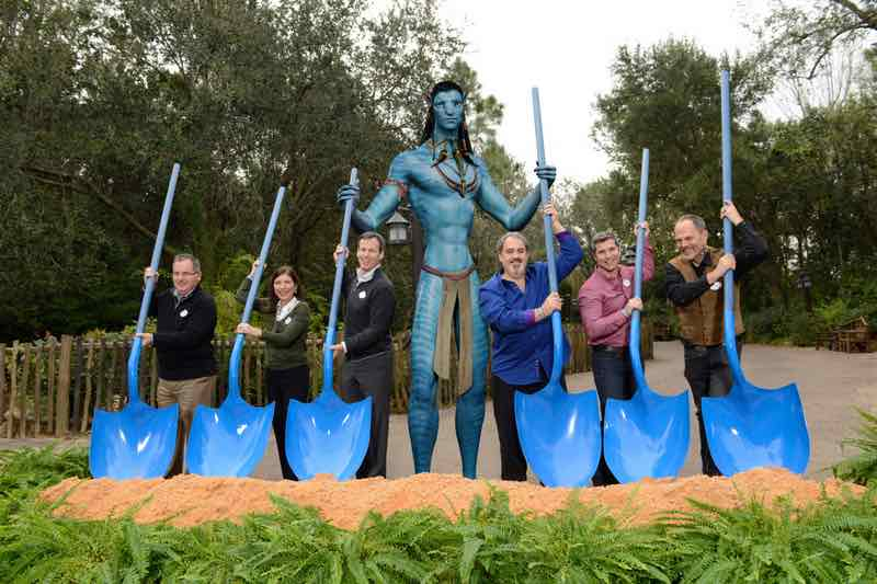 Using Na'vi-inspired shovels and assisted by a Na'vi (photo illustration), (left to right) George Kalogridis, president of Walt Disney World Resort; Meg Crofton, president of Walt Disney Parks and Resorts Operations, United States and France; Tom Staggs, chairman, Walt Disney Parks and Resorts; a Na'vi; Jon Landau, AVATAR Producer; Bruce Vaughn, chief creative executive of Walt Disney Imagineering; and Joe Rohde, creative executive, Walt Disney Imagineering, pose Jan. 8, 2014 during the ceremonial groundbreaking of an AVATAR-inspired land at Disney's Animal Kingdom in Lake Buena Vista, Fla. The multi-year and largest expansion in Disney's Animal Kingdom history, the new land will invite Walt Disney World Resort guests to experience the wonders of Pandora when they fly with the banshees, encounter the Na'vi and explore a rich cultural environment with mountains that float and interactive plants that glow at night. (David Roark, photographer)